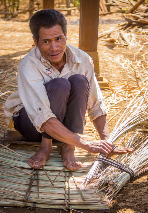 Preparing new roofing for his hut.